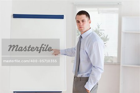 Businessman pointing at something important at flip chart