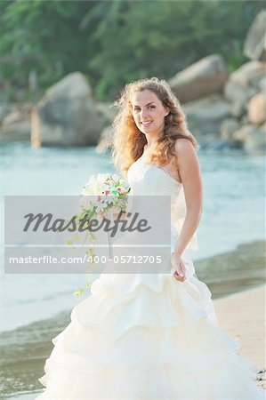 Bride with bouquet on the beach. Tropical wedding