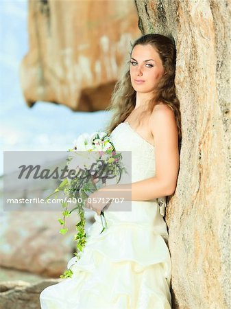 Beautiful bride with bouquet near the sea