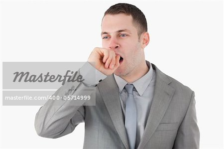 Tired businessman yawning against a white background