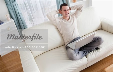 Man enjoying using a notebook in his living room