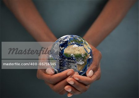 Feminine hands holding the Earth against a dark background