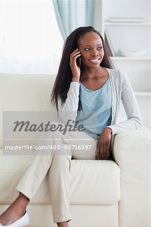 Close up of smiling woman with cellphone on sofa