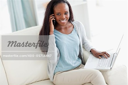 Smiling woman on sofa with laptop and cellphone