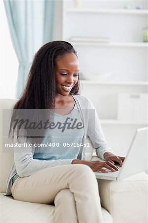 Close up of smiling woman on sofa working on laptop