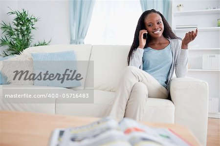 Smiling woman with her cellphone on sofa