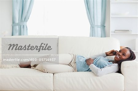 Smiling woman lying on sofa with mobile phone