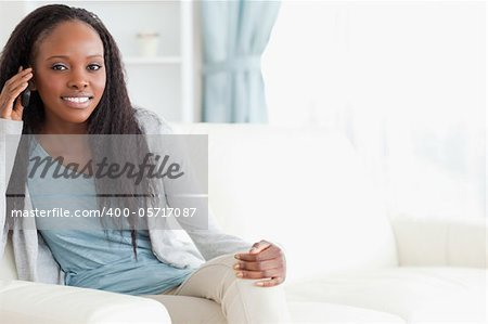 Smiling woman sitting on sofa while using her phone