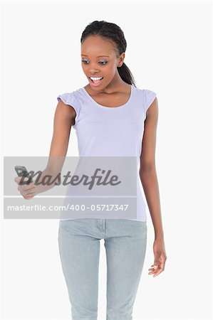 Close up of young woman being surprised by text message on white background