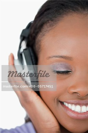 Close up of smiling young woman listening to music on white background