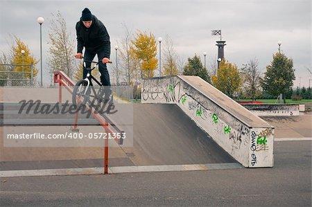 Biker doing crank slide grind trick down to red rail