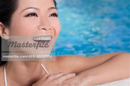 A beautiful sexy young Chinese Asian Oriental woman wearing a bikini and relaxing on the side of a swimming pool.