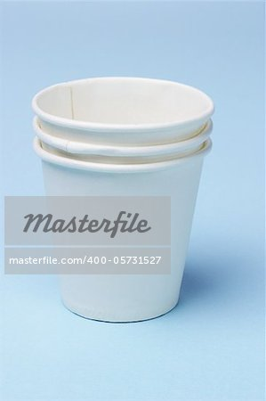 Stack of disposable paper cups on blue background