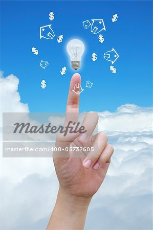 hand holding light bulb and model of a house with dollar symbol on sky