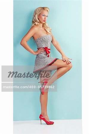 pinup style  full body portrait of a beautiful and sexy blond girl wearing a very short dress black and white with red belt