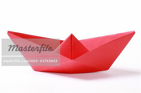 Closeup of a red paper boat on white background