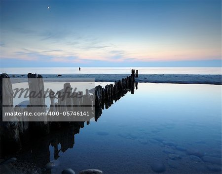 breakwater late one evening with a man fishing in the water and the moon up Stock Photo - Royalty-Free, Artist: ckkeller, Code: 400-05746141