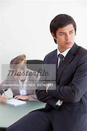 Portrait of a manager posing while his colleague is working in an office