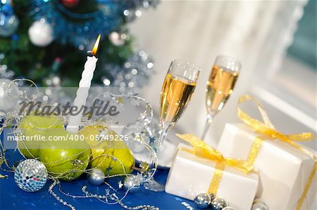 Image of holiday table with flutes of champagne, fruits, gifts, burning candle and decorations on it