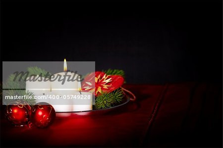 Image of holiday composition with burning candles, decorative balls and coniferous branches on it