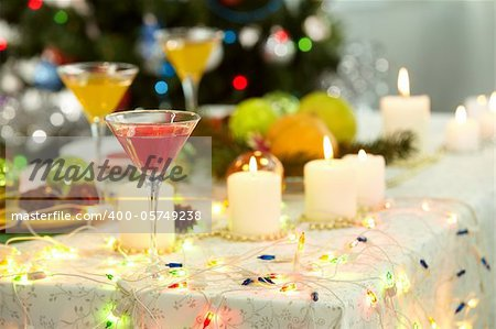 Image of holiday objects: cocktails, burning candles and Christmas decorations