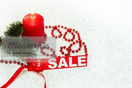 Image of Christmas composition with burning candle, coniferous branch and red label of sale