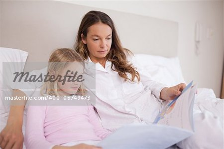 Girl reading a book with her mother in a bedroom