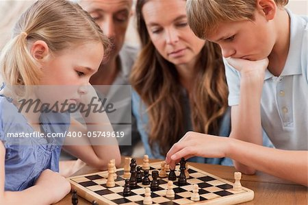 Close up of serious children playing chess in front of their parents in a living room