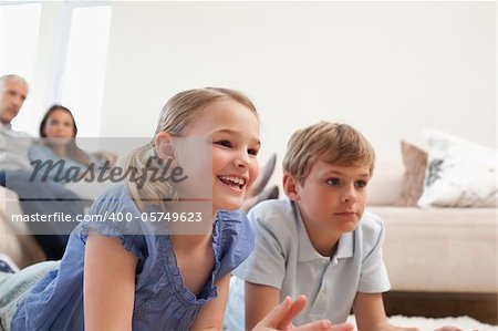 Children playing video games while their parents are watching in a living room