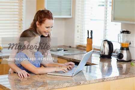 Mother and daughter together with laptop in the kitchen