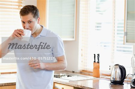 Man having a sip of coffee standing in the kitchen