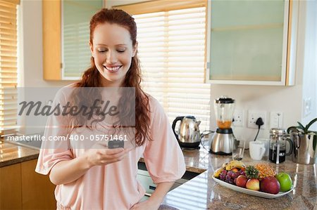 Smiling woman in the kitchen writing text message