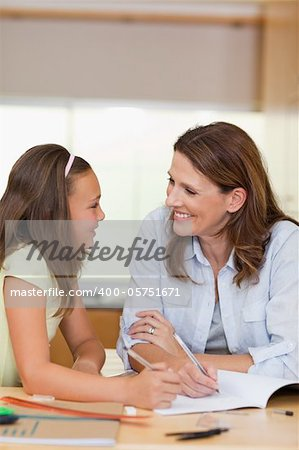 Woman doing homework together with her daughter