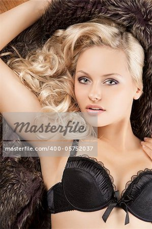 close up portrait of young beautiful girl with blond curly hair wearing a black bra laying on fur