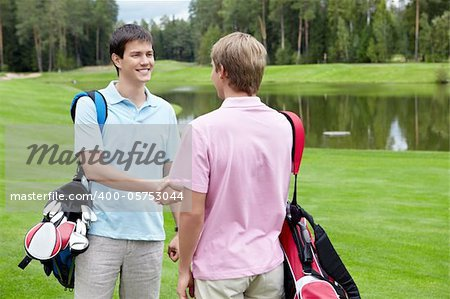 Men shake hands on the golf course