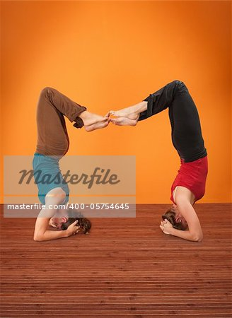 Two women perform Vrisikasana yoga posture on a wooden mat Stock Photo - Budget Royalty-Free, Image code: 400-05754645