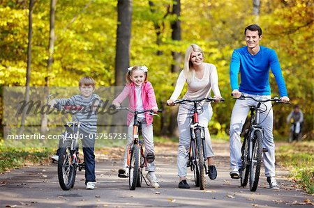 Family on bikes in the park in autumn