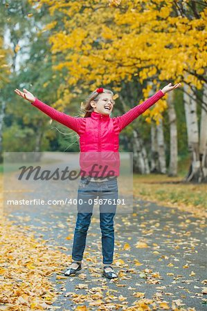 Cute girl walking in the autumn park. Rain, yellow leaves, tree. Stock Photo - Budget Royalty-Free, Image code: 400-05876191