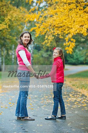 Cute girl with her mother walking in the autumn park. Rain, yellow leaves, tree. Stock Photo - Budget Royalty-Free, Image code: 400-05876195