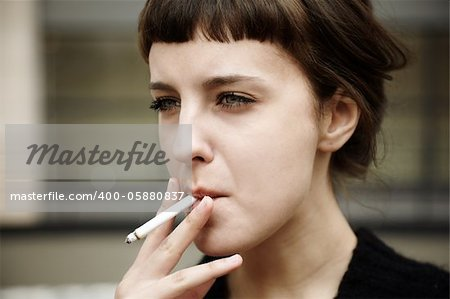 real young woman smokes on the street, selective focus Stock Photo - Budget Royalty-Free, Image code: 400-05880837