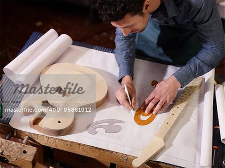 mid adult man at work as craftsman in italian workshop with guitars and blueprints, drawing sketches. High angle view Stock Photo - Budget Royalty-Free, Image code: 400-05881012