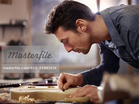 mid adult man at work as craftsman in italian workshop with guitars and musical instruments, smoothing guitar body Stock Photo - Budget Royalty-Free, Image code: 400-05881014