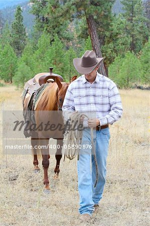Young cowboy leading his horse through the field Stock Photo - Budget Royalty-Free, Image code: 400-05890876