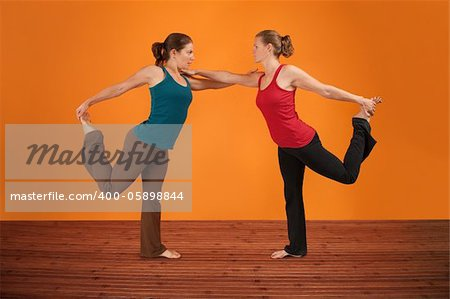 Two Caucasian women perform yogasana over orange background Stock Photo - Budget Royalty-Free, Image code: 400-05898844