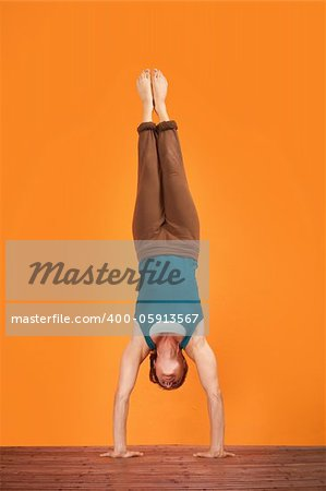 Woman does Adho Mukha Vriksasana yogasana upside down Stock Photo - Budget Royalty-Free, Image code: 400-05913567