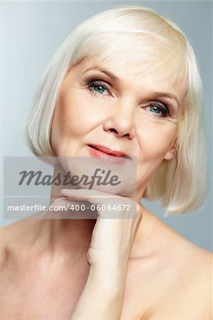 Woman of senior age holding her head gracefully and looking at camera with a smile Stock Photo - Budget Royalty-Free, Image code: 400-06064672