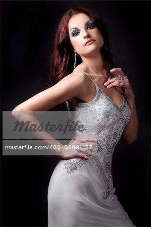 pretty brunette wearing grey fashion dress on black background Stock Photo - Budget Royalty-Free, Image code: 400-06081157