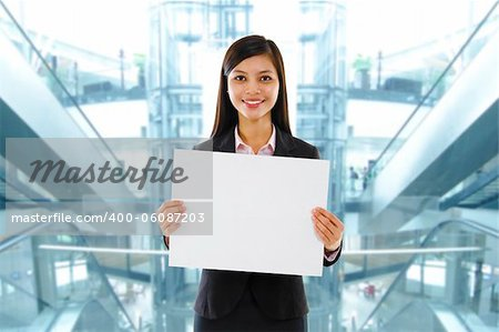 Mixed race Asian businesswoman holding a white board standing inside modern building. Stock Photo - Budget Royalty-Free, Image code: 400-06087203
