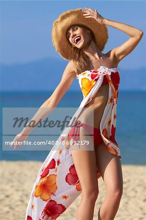 Carefree young woman in a bikini and sarong playing on the beach Stock Photo - Budget Royalty-Free, Image code: 400-06092179
