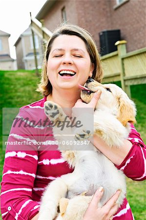 Portrait of laughing woman holding golden retriever puppy Stock Photo - Budget Royalty-Free, Image code: 400-06092347